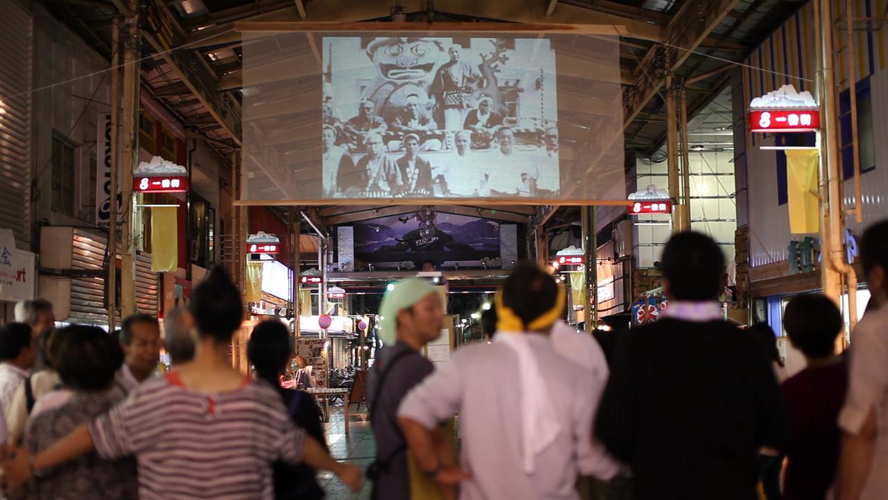 「夜市八島幻燈夜会―よるいちやしまげんとうやかいー」(2012年7月21日)。「種は船」のプロジェクト拠点だった「八島アートポート」のある商店街の夏祭りで「船は種」のチームが現地のメンバーに声をかけられ、(「船は種」のプロジェクト外で)企画した会。商店街の古い写真を集め、アーケードにスクリーンを吊り、そこに投影した写真をみた人が語り合う企画を実施した。